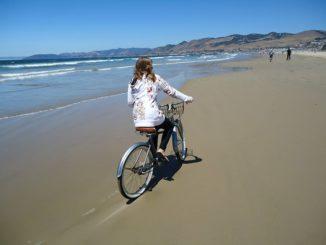 Girl Cycling on Beach